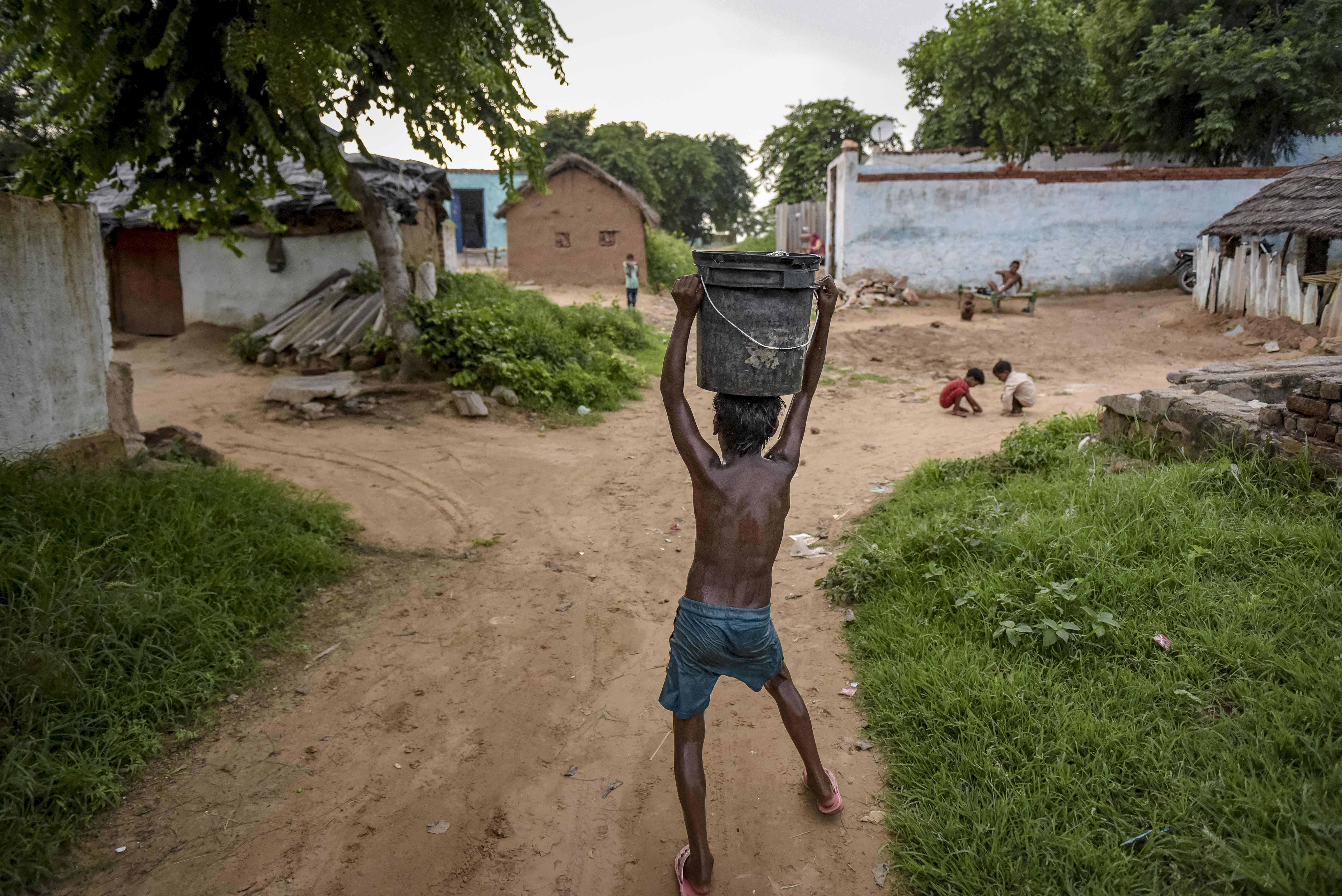 india boy carrying water